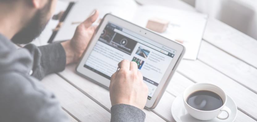 Ein Mann konsumiert Medien auf einem Tablet